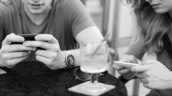Young couple using mobile phones in a cafe.
